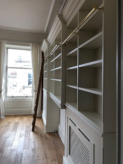 Radiator cover wall unit with bookshelves and library ladder